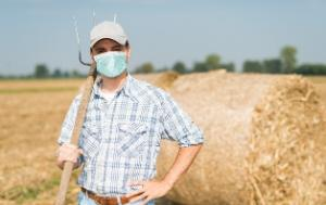 Farmer holding a pitchfork in front of a bale of straw
