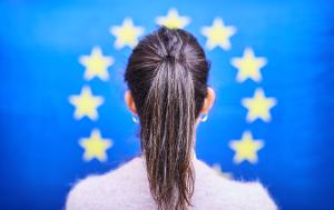 Picture of a woman standing in front of an EU flag.