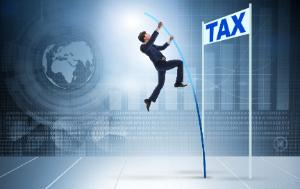 Businessman jumping over a tax sign