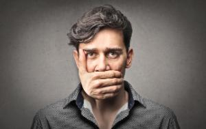 Male person with a hand before his mouth preventing him from speaking