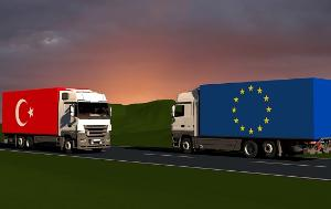 Two trucks crossing each other, one with Turkish flag, the other with EU flag