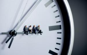 Picture of four people sitting on a clock, showing they are waiting for something.