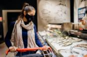 Young woman wearing protective face mask buying fish in a supermarket