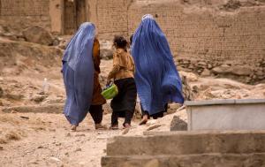Two Afghan women wearing burqa and a girl walking