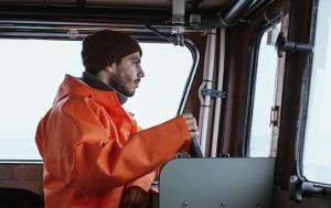 Young fisherman driving fishing boat