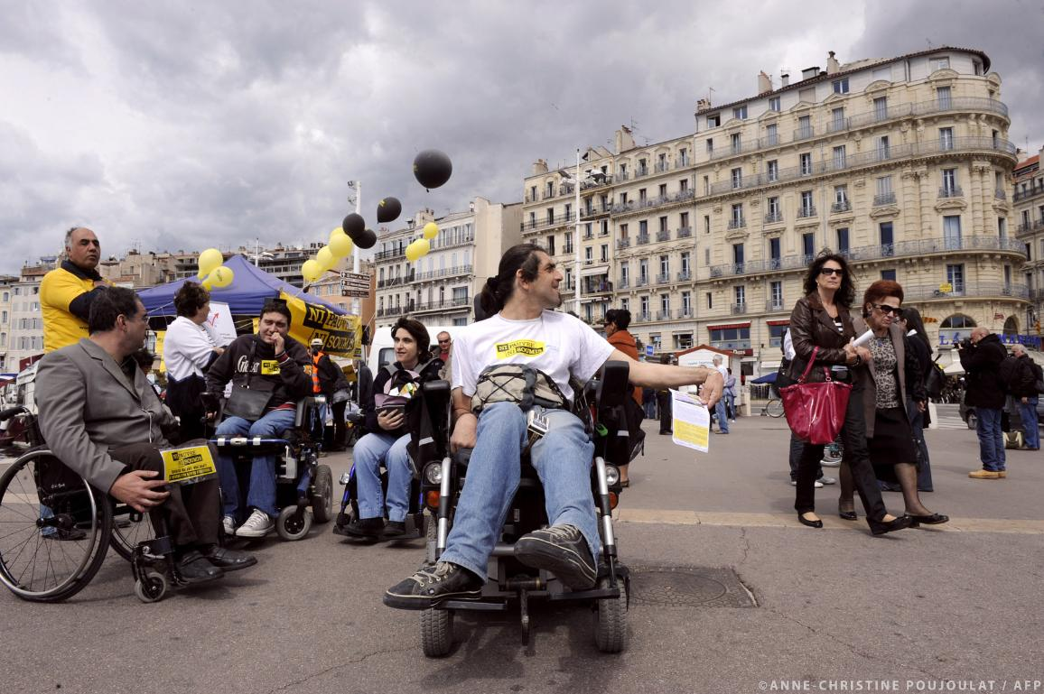People with disabilities distribute leaflets. ©AFP/ANNE-CHRISTINE POUJOULAT
