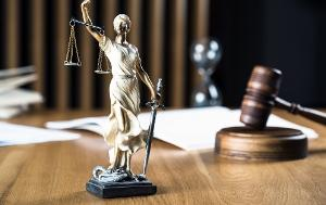 Statue of Lady Justice on a wooden desk with gavel