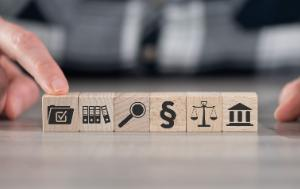 Hands pointing to small wooden cubes with different symbols: compliance, auditing, rule of law
