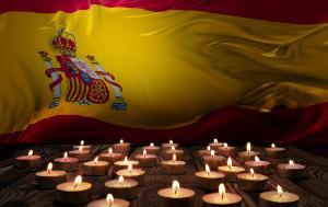 Mourning candles burning on Spain national flag of background.